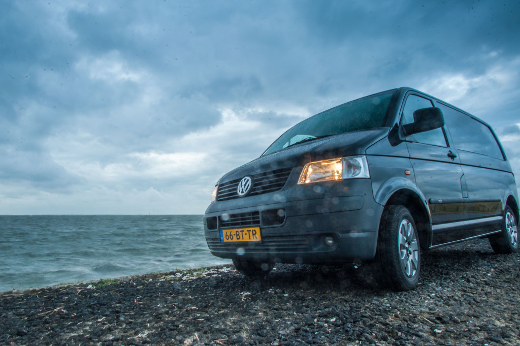 The rough sea, the headlights and the clouds make a great, obscure picture.
